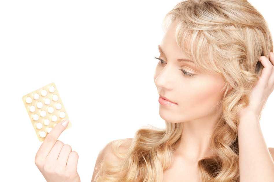 Mujer joven con pastillas anticonceptivas