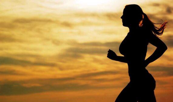 Mujer corriendo con anochecer de fondo